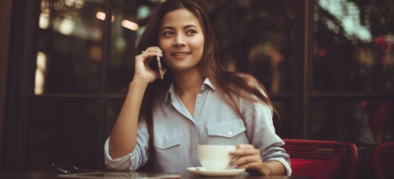 A woman sipping coffee and making a phone call.